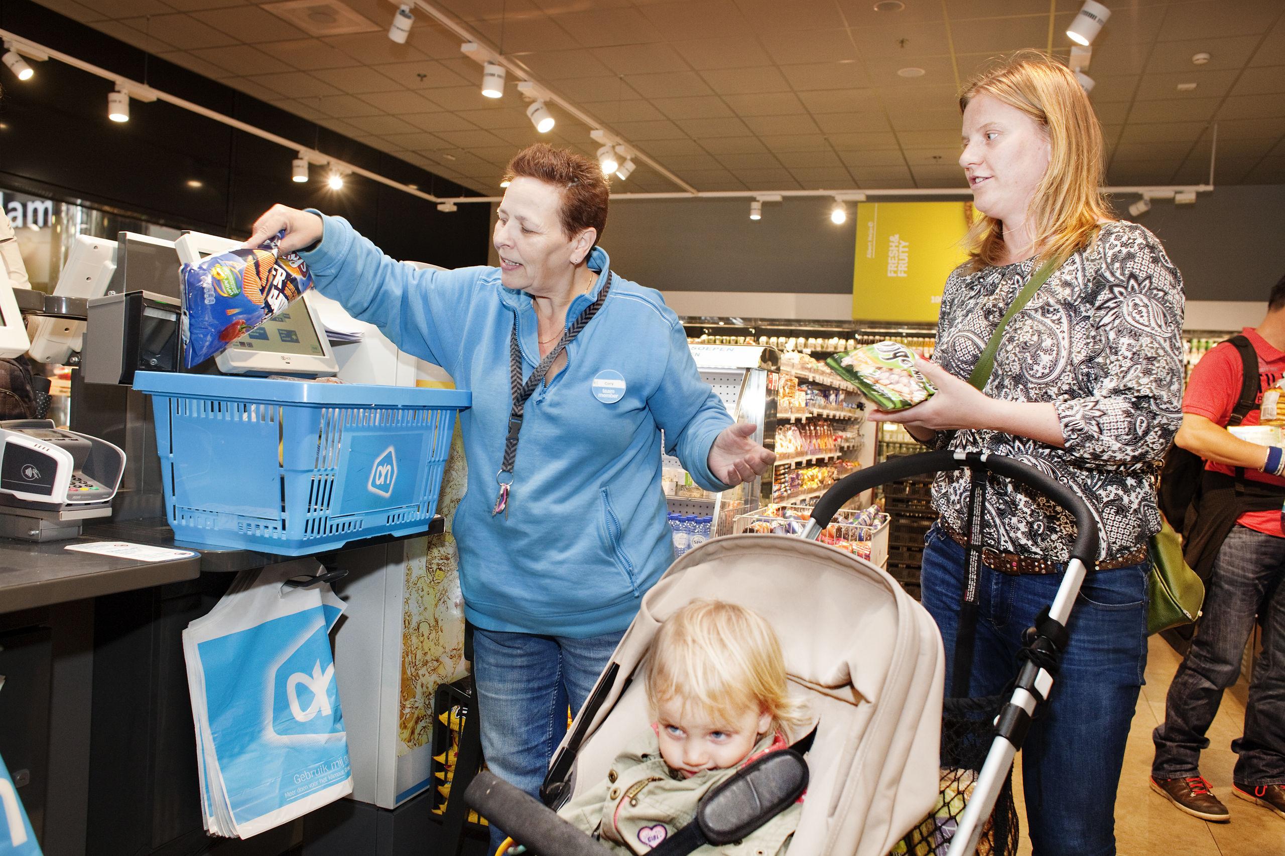 Medewerker in een AH to Go helpt een klant met de zelfscanner. De supermarktbranche pleit al langer voor tijdelijke contracten met een scholingsbudget.